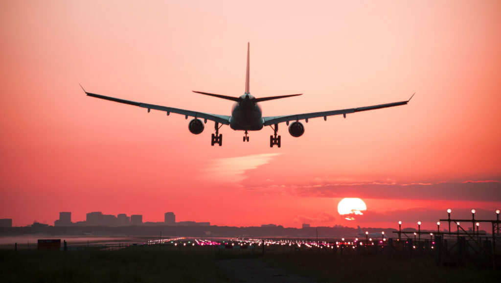 An airplane landing with a beautiful sunset